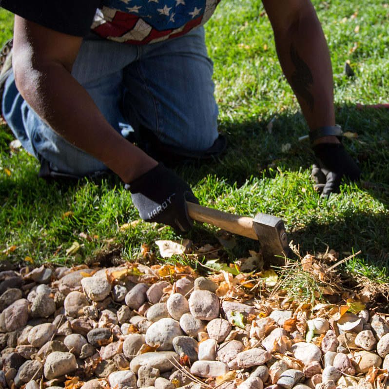 man digging along lawn edge with axe