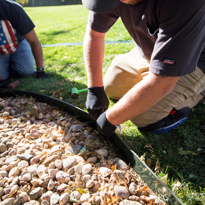 two men placing lawn edging separating rocks and grass